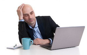 Tired businessman sleeping on a laptop - isolated over white